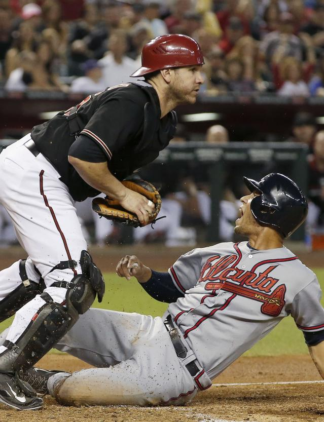 Atlanta Braves' Andrelton Simmons, right, shouts at the umpire as he scores ahead of the tag by Arizona Diamondbacks' Miguel Montero during the third inning of a baseball game Saturday, June 7, 2014, in Phoenix. (AP Photo/Ross D. Franklin)