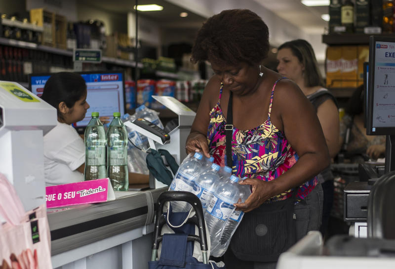 Marcia Helena buys bottled water at a supermarket in the Copacabana neighborhood of Rio de Janeiro, Brazil, Jan. 15, 2020. There's a creeping sense of alarm in Rio de Janeiro after more than a week of foul tasting and smelling tap water in dozens of neighborhoods, and residents are hoarding bottled water. (AP Photo/Bruna Prado)