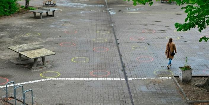 A woman walks in the schoolyard of an elementary school in Berlin where circles have been painted on the ground to mark the recommended distance, in preparation of the return of some pupils from early May 2020 (AFP Photo/Tobias Schwarz)