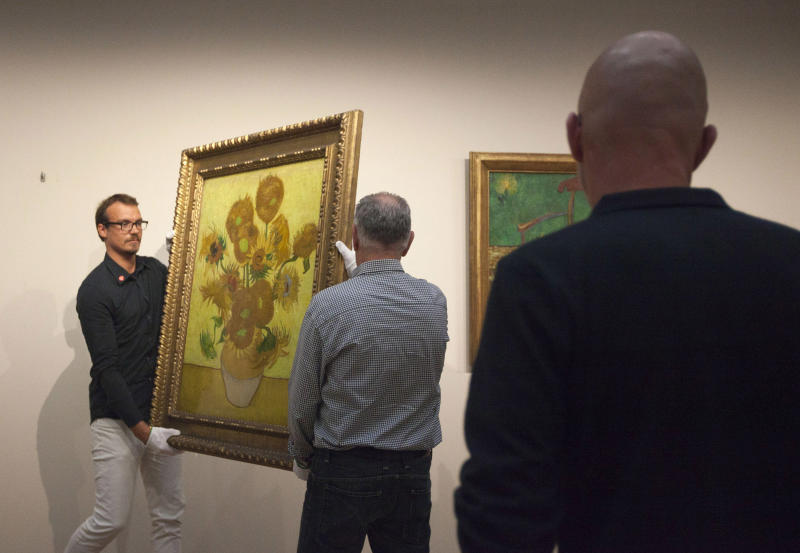 """Curators remove Vincent van Gogh's famous """"Sunflowers"""" painting from the wall of the Van Gogh Museum in Amsterdam, Netherlands, Sunday, Sept. 23, 2012. While the museum closes for seven months for renovations, 75 works by the Dutch painter will be displayed instead across town at The Hermitage, an Amsterdam satellite of the Russian state museum. The tricky process of transporting the artworks under police escort began immediately after the last visitors left the museum Sunday evening and carried on through the night into Monday morning. The Van Gogh Museum reopens April 25, 2013. (AP Photo/Cris Toala Olivares)"""