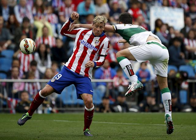 Atletico Madrid's Fernando Torres (L) fights for the ball with Elche's Domingo Cisma during their Spanish first division soccer match at Vicente Calderon stadium in Madrid, April 25, 2015. REUTERS/Susana Vera