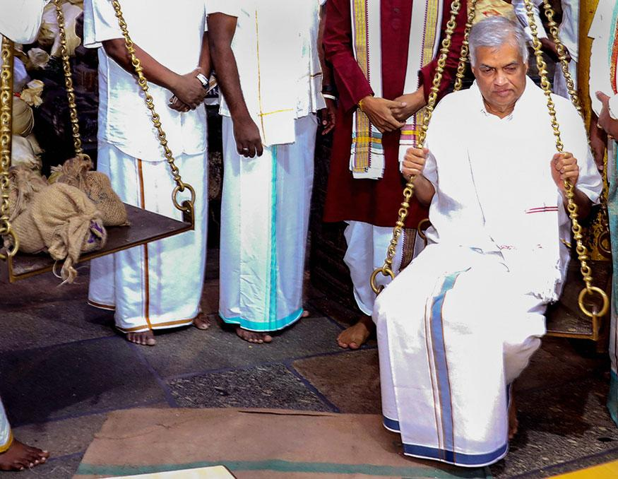 Sri Lankan Prime Minister Ranil Wickremesinghe sits on a scale making an offering under 'Thulabaram' practice, at Lord Venkateswara temple at Tirumala in Tirupati. (Image: PTI)