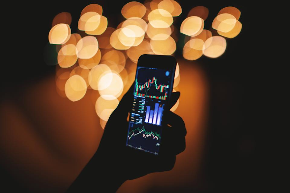 Silhouette of female hand holding smart phone in the dark with stock trading on display with light bokeh blurred background, Mobile business concept