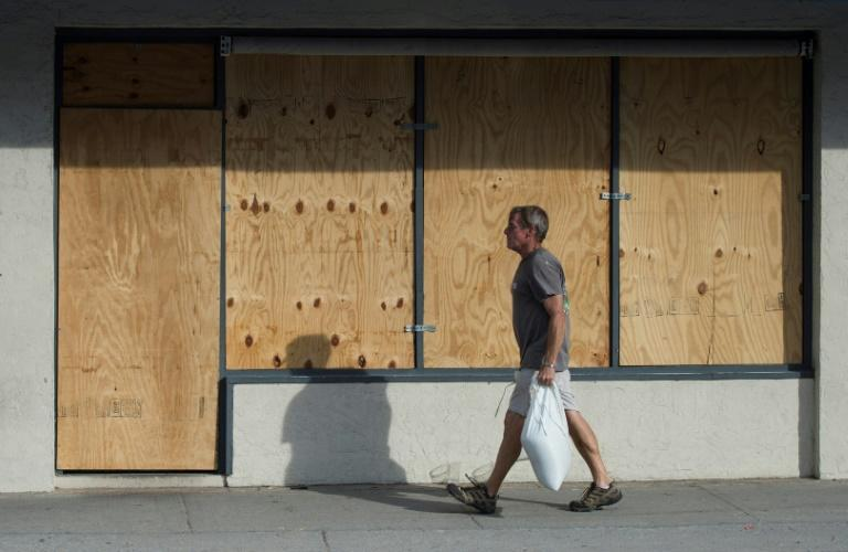 A man carries sandbags past a boarded up shop days before the arrival of hurricane Florence at Wrightsville Beach, North Carolina
