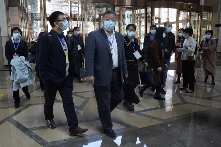 """Chinese attendees, some wearing tags which reads """"Expert Team,"""" walk to a restaurant after leaving a conference area where World Health Organization team of researchers are meeting their Chinese counterparts in Wuhan in central China's Hubei province on Friday, Jan. 29, 2021. World Health Organization experts are to begin face-to-face meetings with their Chinese counterparts Friday in the central city of Wuhan at the start of the team's long-awaited fact-finding mission into the origins of the coronavirus. (AP Photo/Ng Han Guan)"""