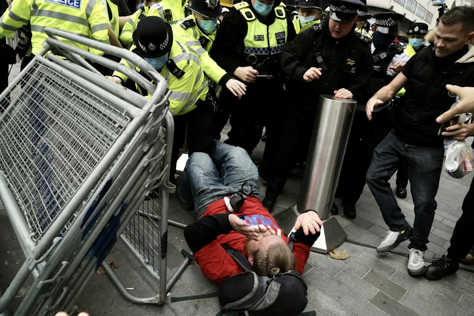 LONDON, UNITED KINGDOM - OCTOBER 17: Police officers intervene in protesters as members of StandUpX stage a protest against coronavirus (Covid-19) measures and vaccine despite social gatherings of more than six people are not be allowed within Covid-19 measures in London, United Kingdom on October 17, 2020. (Photo by Hasan Esen/Anadolu Agency via Getty Images)