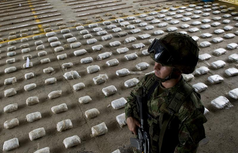 """A Colombian Army soldier stands next to packages of seized cocaine, which according to authorities, belonged to the criminal gang """"Clan Usuga"""" and was going to be sent to Central America, at a Military Base in Bahia Solano, Colombia on March 14, 2015"""