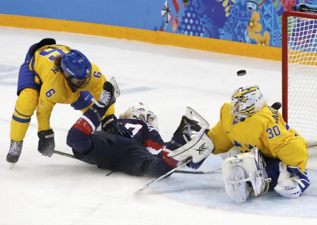 Team USA's Jocelyne Lamoureux is hauled down by Sweden's Lina Backlin (L) as Sweden's goalie Kim Martin Hasson sprawls to make a save during the third period of their women's semi-final ice hockey game at the 2014 Sochi Winter Olympics, February 17, 2014. REUTERS/Grigory Dukor (RUSSIA - Tags: OLYMPICS SPORT ICE HOCKEY)