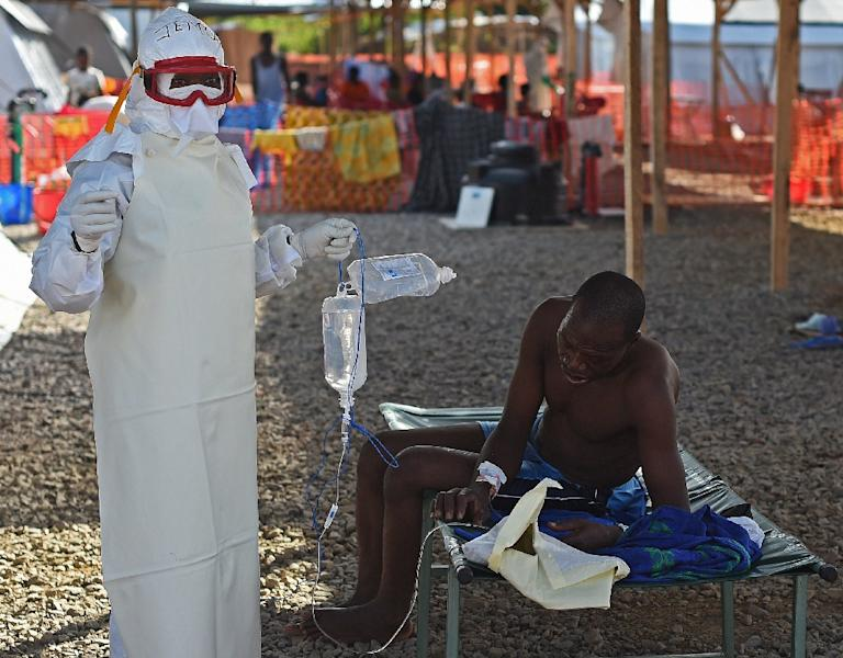 A nurse wearing personal protective equipment assists an ebola patient at the Kenema treatment center in Sierra Leone run by the Red Cross Society on November 15, 2014 (AFP Photo/Francisco Leong)