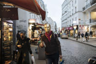 A man wear a golden mask costume walks down a street in Paris, Thursday Oct.29, 2020. Some doctors expressed relief but business owners despaired as France prepared to shut down again for a month to try to put the brakes on the fast-moving virus. The new measures are set to come into effect at midnight. (AP Photo/Lewis Joly)