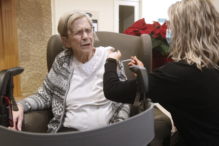 Paramedic Jessi Bittner inoculates Margaret Watson, 94, a resident at Oakview Place Long Term Care Residence, with her COVID-19 vaccine in the Winnipeg care home, Monday, Jan. 11, 2021. Watson was the first member of the public to receive the vaccine in Winnipeg, Manitoba. (John Woods/The Canadian Press via AP)