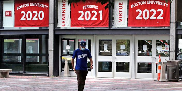 """In this July 23, 2020, file photo, Weston Koenn, a graduate student from Los Angeles, leaves the Boston University student union building as he walks through the student-less campus in Boston. <p class=""""copyright"""">AP Photo/Charles Krupa, File</p>"""