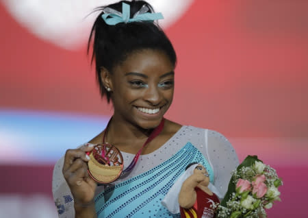 Gold medallist and four-times All-Around world champion Simone Biles of the U.S., poses on the podium after the Women's All-Around Final of the Gymnastics World Chamionships at the Aspire Dome in Doha, Qatar
