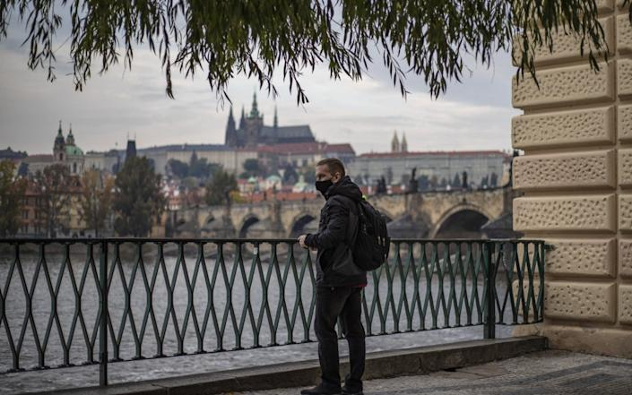 A man wearing protective face mask looks on Vltava river with Prague Castle and Charles Bridge in the background, in Prague, Czech Republic - Martin Divisek/EPA-EFE/Shutterstock