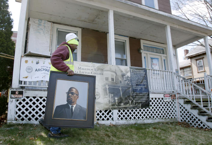 FILE - In this March 29, 2016, file photo, Rodnell P. Collins carries a painting of his uncle, Malcolm X outside the house where the slain African-American activist spent part of his teen years in the Roxbury neighborhood of Boston. According to the National Park Service the house was added to the National Register of Historic Places in February 2021. (AP Photo/Bill Sikes, File)