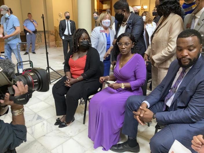 Relatives of Ahmaud Arbery including sister Jasmine Arbery, left, and mother Wanda Cooper Jones, second from left, sit at the Georgia state capitol in Atlanta on Monday, May 10, 2021. They witnessed Georgia Gov. Brian Kemp sign a law repealing citizen's arrest in Georgia, partly blamed for Ahmaud Arbery's fatal shooting death near Brunswick in 2020. (AP Photo/Jeff Amy)