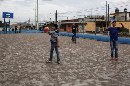Children play in a basketball court covered with ash after Guatemala's Fuego volcano erupted violently, in Guatemala City, Guatemala June 3, 2018. REUTERS/Luis Echeverria