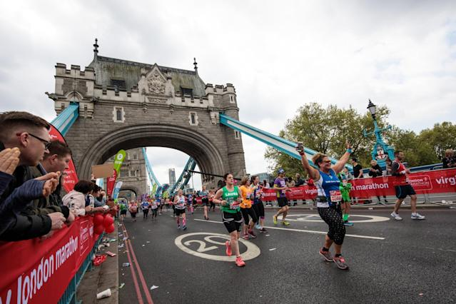 <p>Runners at the London Marathon celebrate as supporters watch on </p>