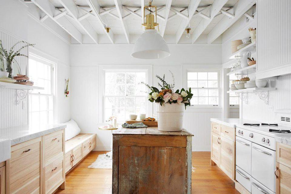 "<p>Leanne Ford is the queen of revamping beat up and outdated things. Case in point? This rustic kitchen island. The tin bucket also looks upscale filled with a gorgeous bouquet of roses, as do the walls, thanks to a fresh coat of paint—in <a href=""https://www.housebeautiful.com/design-inspiration/a27424763/nate-berkus-jeremiah-brent-leanne-ford-favorite-paint-color/"" rel=""nofollow noopener"" target=""_blank"" data-ylk=""slk:Ford's favorite color."" class=""link rapid-noclick-resp"">Ford's favorite color.</a> </p>"