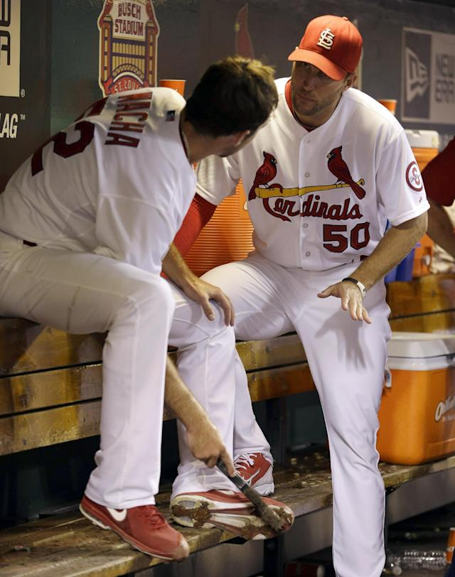 St. Louis Cardinals' Adam Wainwright, right, talks with starting pitcher Michael Wacha in the dugout during the third inning of a baseball game against the Washington Nationals, Tuesday, Sept. 24, 2013, in St. Louis. (AP Photo/Jeff Roberson)