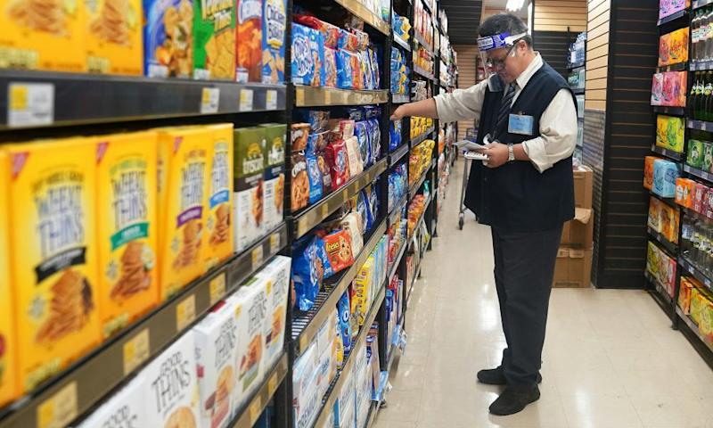 A worker wearing a face shield checks products at a grocery store in New York, New York.