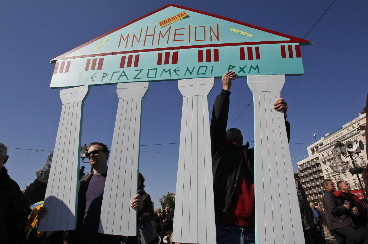 Employees of the Byzantine and Christianity museum hold a cardboard replica of ancient ruins which reads: ''Monument for sale'' during a peaceful protest outside the Greek Parliament in Athens, Sunday, Feb. 19, 2012. Tensions between Athens and other European capitals hit new highs this week as eurozone ministers delayed to next Monday a decision on a bailout agreement and demanded more commitments from Greece. (AP Photo/Thanassis Stavrakis)