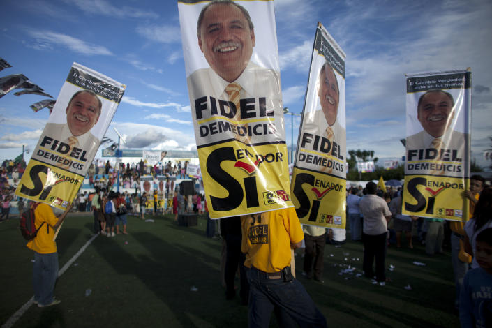 In this photo taken on Thursday, June 21, 2012, Democratic Revolution Party, PRD, supporters hold banners of senatorial candidate Fidel Demedicis during a campaign rally on a soccer field, in Temixco, on the outskirts of Cuernavaca, Mexico. As Mexicans head to the ballot box Sunday, drug cartels are registering their votes with scare tactics and cold, hard cash to make sure whoever is elected doesn't interfere with their lucrative operations. (AP Photo/Alexandre Meneghini)