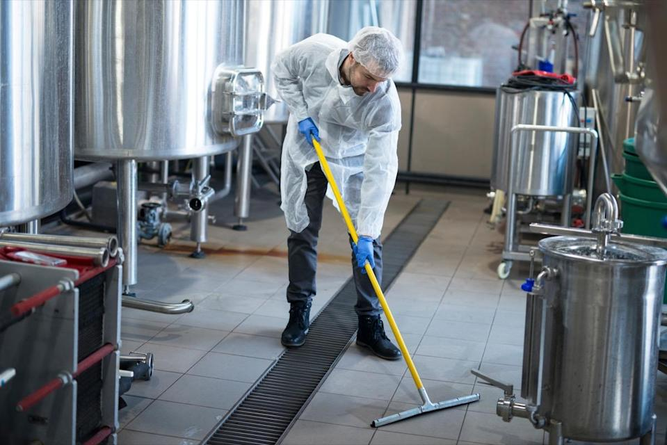 Professional cleaner wearing protection uniform cleaning floor of production plant