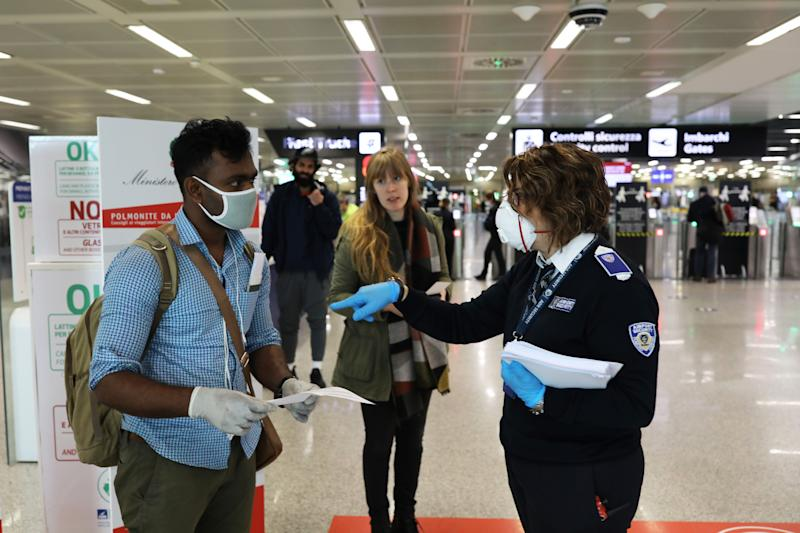 ROME, ITALY - MARCH 17: A member of a Bangladeshi family seeks help to an employee of ADR, Aeroporti di Roma, to fill out a self-certification that certifies their motivation to violate the quarantine so they can travel at Terminal 3 of the Leonardo Da Vinci international airport of Rome Fiumicino on March 17, 2020 in Rome, Italy. One of the two terminals of the Leonardo Da Vinci international airport of Rome Fiumicino, the terminal 1 usually dedicated to domestic flights closes temporarily due to the Coronavirus emergency, the little air traffic left has been moved to Terminal 3. (Photo by Marco Di Lauro/Getty Images) (Photo: Marco Di Lauro via Getty Images)
