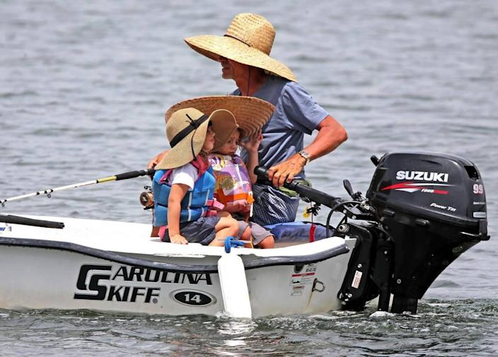 On June 21, 2021, a fisherman with two girls wearing wide-brimmed hats, all shaded from the sun, goes fishing near the Howrover Sandbar in Miami-Dade, Florida.
