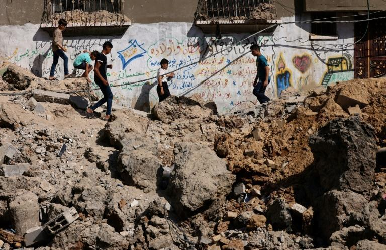 Palestinian children walk amid the rubble of buildings destroyed by Israeli strikes in Beit Hanun in the northern Gaza Strip on May 21