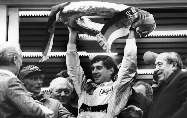 FILE - In this May 13, 1984, file photo, Brazilian Formula One race driver Ayrton Senna da Silva, center, holds up the winner's crown after he won the Mercedes 190 E race in Nuremberg, Germany ahead of former world champion Niki Lauda, second from left. At the right, smiling German transport minister Werner Dollinger. Senna won three Formula One titles in 1988, 1990 and '91 all with McLaren. He moved to the Williams team for his tragic 1994 season. Despite his career being cut short when he was 34, his 41 wins stand third all-time behind Michael Schumacher's 91 and rival Alain Prost's 51. He died at the 1994 San Marino Grand Prix. (AP Photo/Udo Weitz, File)