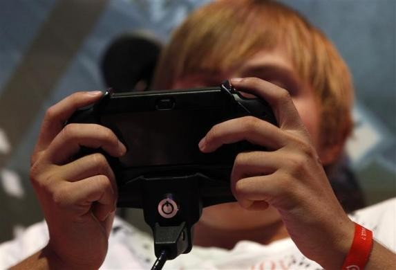 A visitor plays a Playstation PS Vita during the Gamescom 2012 fair in Cologne August 16, 2012.