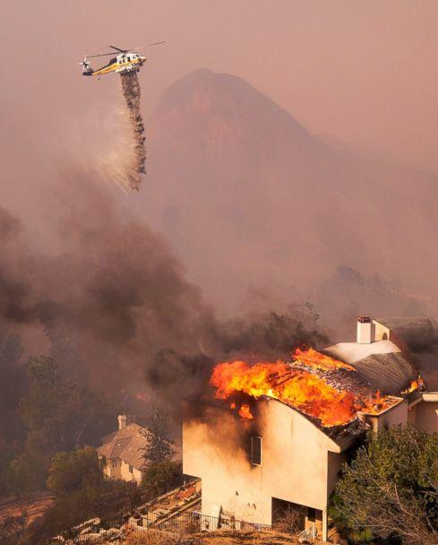PHOTO: A helicopter drops water while a wildfire burns a home near Malibu Lake in Malibu, Calif., Friday, Nov. 9, 2018. (AP)