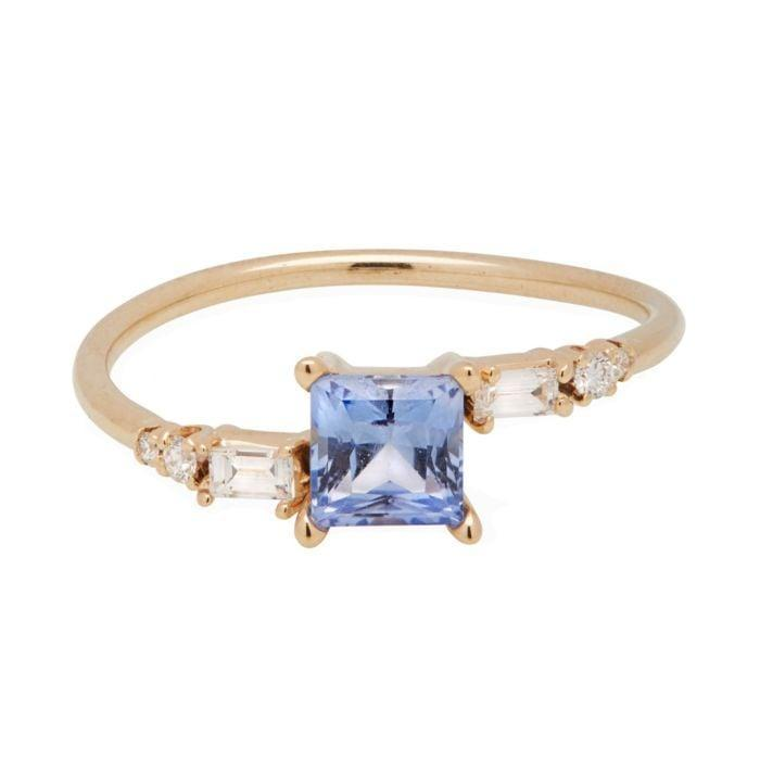 """<p>This dreamy blue sapphire <a href=""""https://www.popsugar.com/buy/One-Kind-Blue-Princess-Crossover-Ring-531757?p_name=One%20of%20a%20Kind%20Blue%20Princess%20Crossover%20Ring&retailer=catbirdnyc.com&pid=531757&price=3%2C565&evar1=fab%3Aus&evar9=47015200&evar98=https%3A%2F%2Fwww.popsugar.com%2Ffashion%2Fphoto-gallery%2F47015200%2Fimage%2F47015961%2FColored-Stones-One-Kind-Blue-Princess-Crossover-Ring&list1=shopping%2Cjewelry%2Crings%2Cengagement%20rings&prop13=mobile&pdata=1"""" rel=""""nofollow noopener"""" class=""""link rapid-noclick-resp"""" target=""""_blank"""" data-ylk=""""slk:One of a Kind Blue Princess Crossover Ring"""">One of a Kind Blue Princess Crossover Ring</a> ($3,565) is highlighted by small diamonds on each side.</p>"""