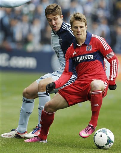 Chicago Fire midfielder Chris Rolfe, front, is covered by Sporting Kansas City defender Matt Besler during the first half of an MLS soccer match in Kansas City, Kan., Saturday, March 16, 2013. (AP Photo/Orlin Wagner)