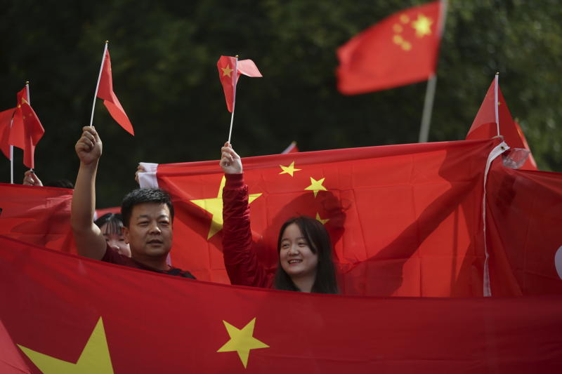 "FILE - In this Aug. 17, 2019, file photo, pro-China counter-protesters hold Chinese flags during an anti-extradition rally for Hong Kong in Vancouver. Governments around the world are taking a cautious approach to responding to the protests roiling Hong Kong. With the notable exception of Taiwan, cautious comments from a handful of governments fall short of support for the demonstrators. They are so mild that even the word ""protest"" itself was left out of the joint EU-Canada statement that was the most recent to infuriate the Chinese government. Most are unwilling to risk that fury at all, showing China's deep influence around the world. (Darryl Dyck/The Canadian Press via AP, File)"