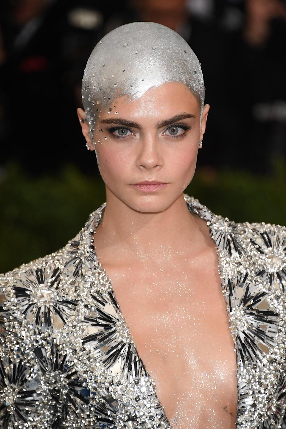 <p>Delevingne debuted her newly shaved head in the most epic way possible at the 2017 Met Gala. Makeup artist Romy Soleimani <span>combined Mehron Silver Metallic Powder with MAC Mixing Medium</span>, and painted the mixture over her bald head, letting it dip down onto her forehead, creating the outline of where a fringe might be. Soleimani then topped off the silver paint with glitter hairspray (to add dimension) and finished with a smattering of Swarovski crystals that she stuck on with Spirit Gum.</p>