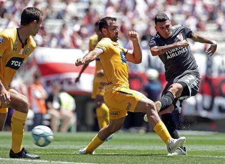 Matias Suarez R kicks the ball next to Rosario Central's midfielder F.jpg