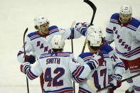 New York Rangers' Brett Howden, left, celebrates with teammates after assisting a goal by Vitali Kravtsov during the first period of the NHL hockey game against the New Jersey Devils in Newark, N.J., Sunday, April 18, 2021. (AP Photo/Seth Wenig)