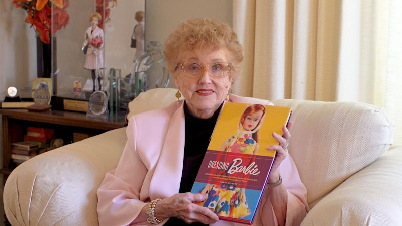 "Carol Spencer sits in her living room with her book, ""Dressing Barbie""."