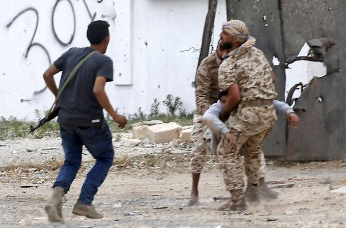 Fighters loyal to the Libyan internationally-recognised Government of National Accord (GNA) carry a wounded comrade during clashes against forces loyal to strongman Khalifa Haftar, on May 21, 2019 in the Salah al-Din area south of the Libyan capital Tripoli. (Photo: Mahmud Turkia/AFP/Getty Images)
