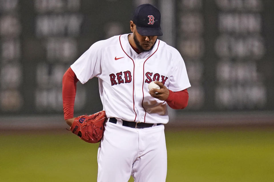 Boston Red Sox starting pitcher Eduardo Rodriguez looks down at a fresh baseball after giving up a solo home run to Oakland Athletics' Matt Olson during the sixth inning of a baseball game, Wednesday, May 12, 2021, in Boston. (AP Photo/Charles Krupa)