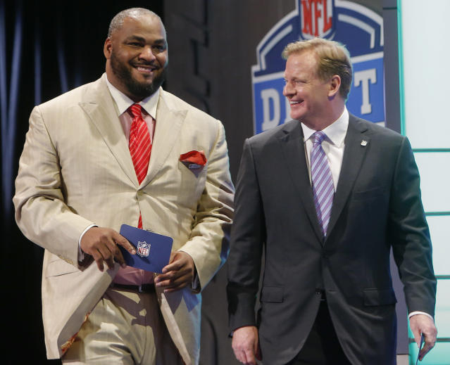 Former Seattle Seahawks linebacker Walter Jones walks out on stage with NFL commissioner Roger Goodell to announce the Seahawks pick for the second round of the 2014 NFL Draft, Friday, May 9, 2014, in New York. (AP Photo/Jason DeCrow)