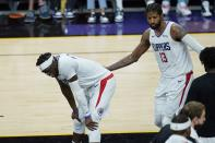 Los Angeles Clippers guard Paul George (13) and Clippers guard Reggie Jackson, left, pause on the court during the second half of Game 1 of the NBA basketball Western Conference finals against the Phoenix Suns, Sunday, June 20, 2021, in Phoenix. (AP Photo/Ross D. Franklin)