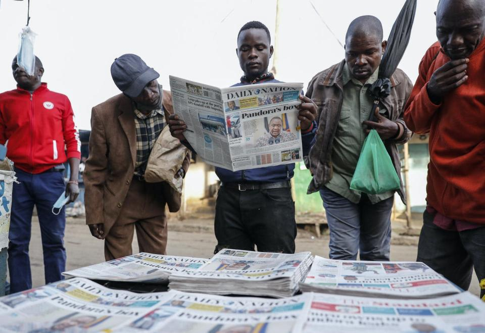 A group of men gather around a selection of newspapers, one of them reading one.