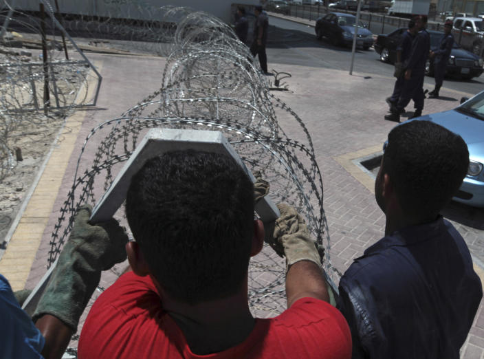 Police install razor wire across a street between a village and main road on the outskirts of Manama, Bahrain, on Tuesday, Aug. 13, 2013. Bahraini authorities are stepping up security ahead of plans announced by the anti-government opposition to launch a major rebellion Wednesday against the Gulf monarchy. (AP Photo/Hasan Jamali)