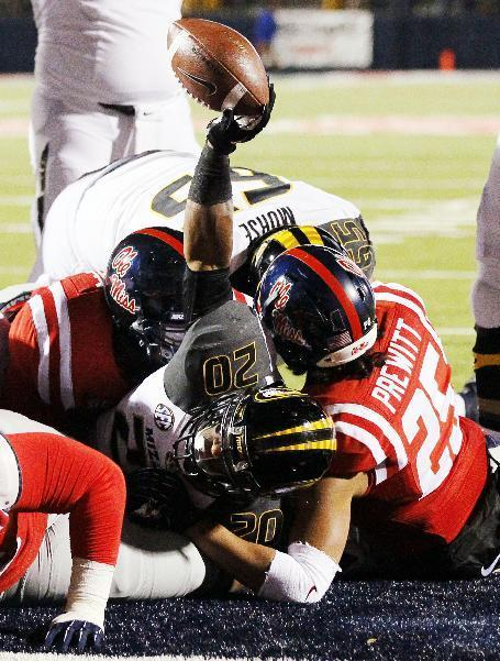 Missouri running back Henry Josey (20) holds the ball in the air after scoring a first quarter touchdown over Mississippi defensive back Cody Prewitt (25) during an NCAA college football game Saturday, Nov. 23, 2013, in Oxford, Miss. (AP Photo/Rogelio V. Solis)