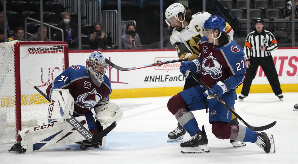 Colorado Avalanche goaltender Philipp Grubauer, left, stops a shot as defenseman Ryan Graves, front right, works against Vegas Golden Knights left wing Max Pacioretty during the first period of Game 5 of an NHL hockey Stanley Cup second-round playoff series Tuesday, June 8, 2021, in Denver. (AP Photo/David Zalubowski)