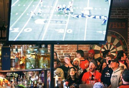 FILE PHOTO - Denver Broncos fans react to a play while watching their team's NFL Super Bowl XLVIII football game against the Seattle Seahawks at the View House bar in Denver, Colorado February 2, 2014. REUTERS/Marc Piscotty